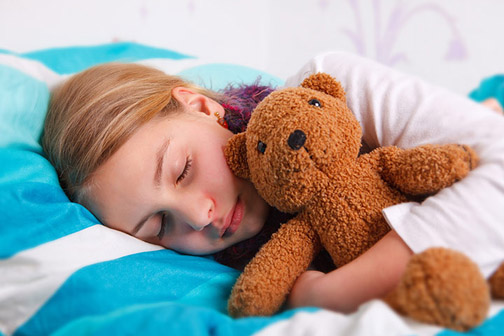 Child sleeping with soft toy