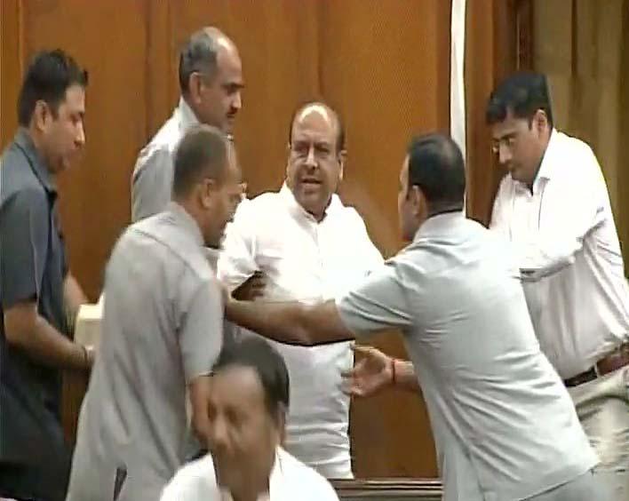 Bharatiya Janata Party MLA Vijendra Gupta being marshaled out from Delhi Assembly