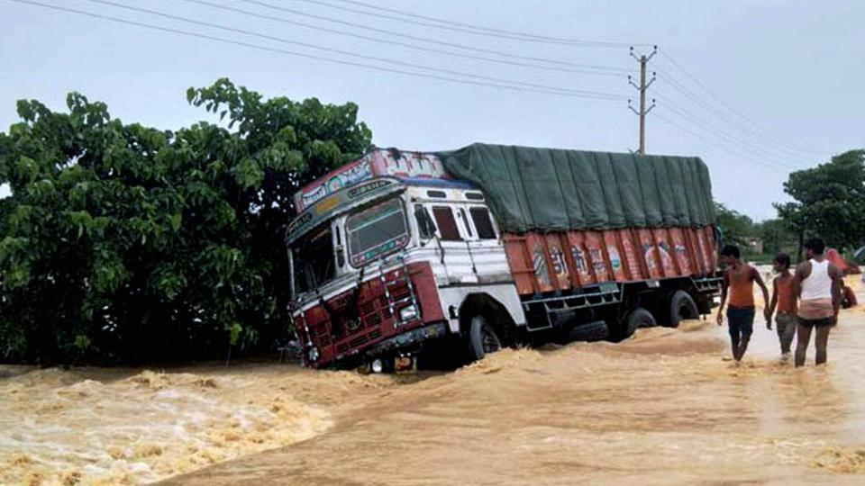 A truck drifts off the submerged NH 28 at flooded Ramgadhwa in East Champaran