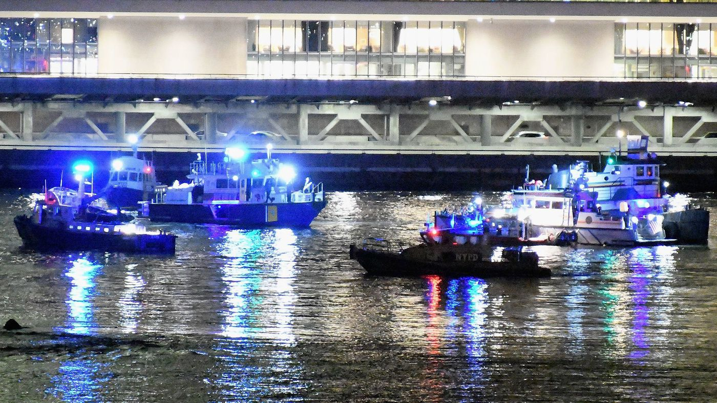 Emergency personnel work at the scene of a helicopter crash in the East River in New York