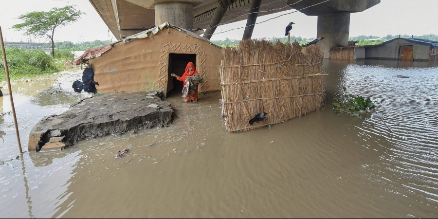 A woman stands outside her submerged shanty at Yamuna Khadar as the water level of Yamuna river rises in New Delhi