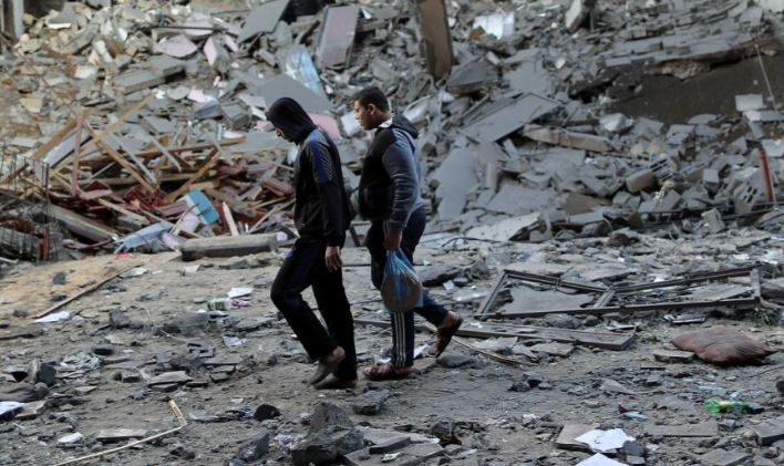 Palestinians walk past the remains of the building