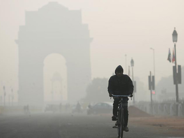 A man rides his bicycle in front of the India Gate shrouded in smog in New Delhi