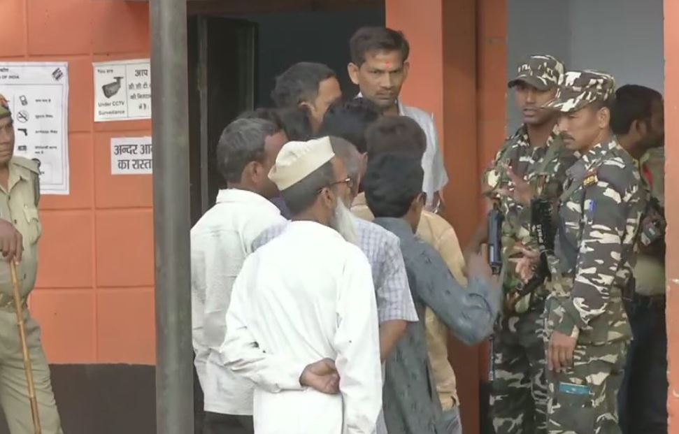 Voters queue up outside polling booth number 256 in Kannauj