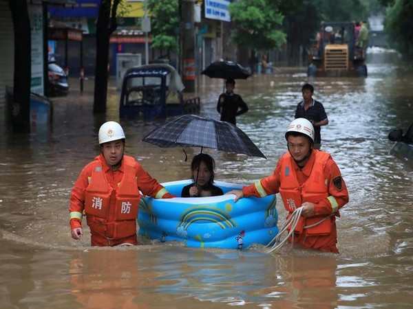 A woman being rescued by emergency workers in China's Jiangxi province