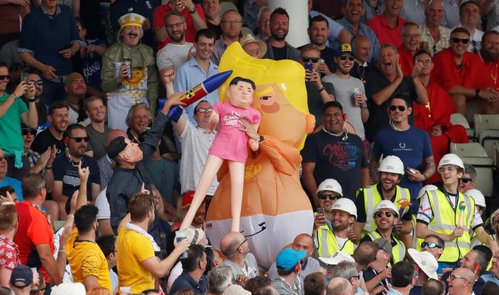A man dressed as the Trump baby blimp holding a Kim Jong-un dummy