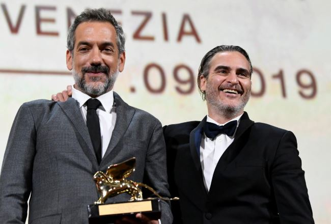 Director Todd Phillips poses next to Joaquin Phoenix after winning the Golden Lion for Best Film.