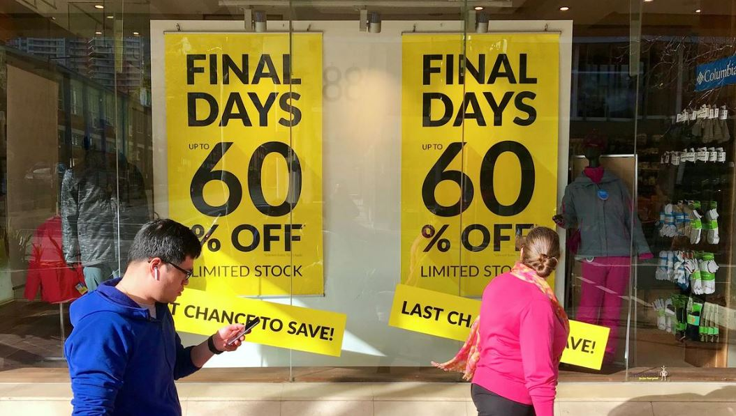 Shoppers walk past sales signs on display in the window