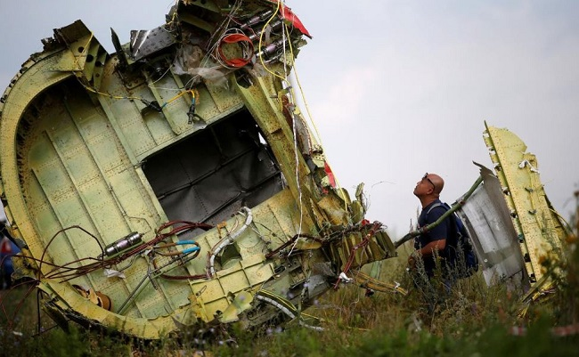 Malaysian air crash investigator inspects the crash site of Malaysia Airlines Flight MH17