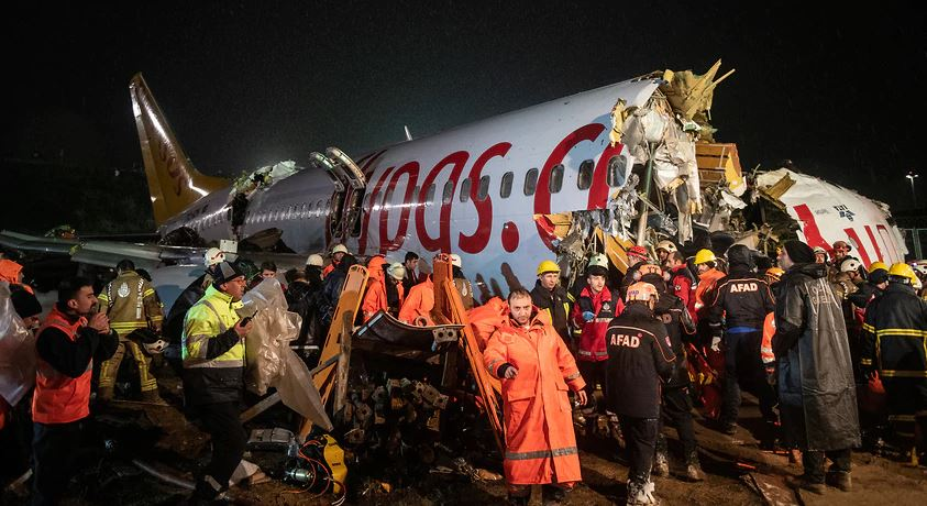 First responders gather around the Pegasus Airlines Boeing 737-86J plane wreckage after it overran the runway during landing and crashed, at Istanbul's Sabiha Gokcen airport