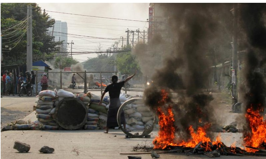 A demonstrator gestures near a barricade during a protest against the military coup in Mandalay