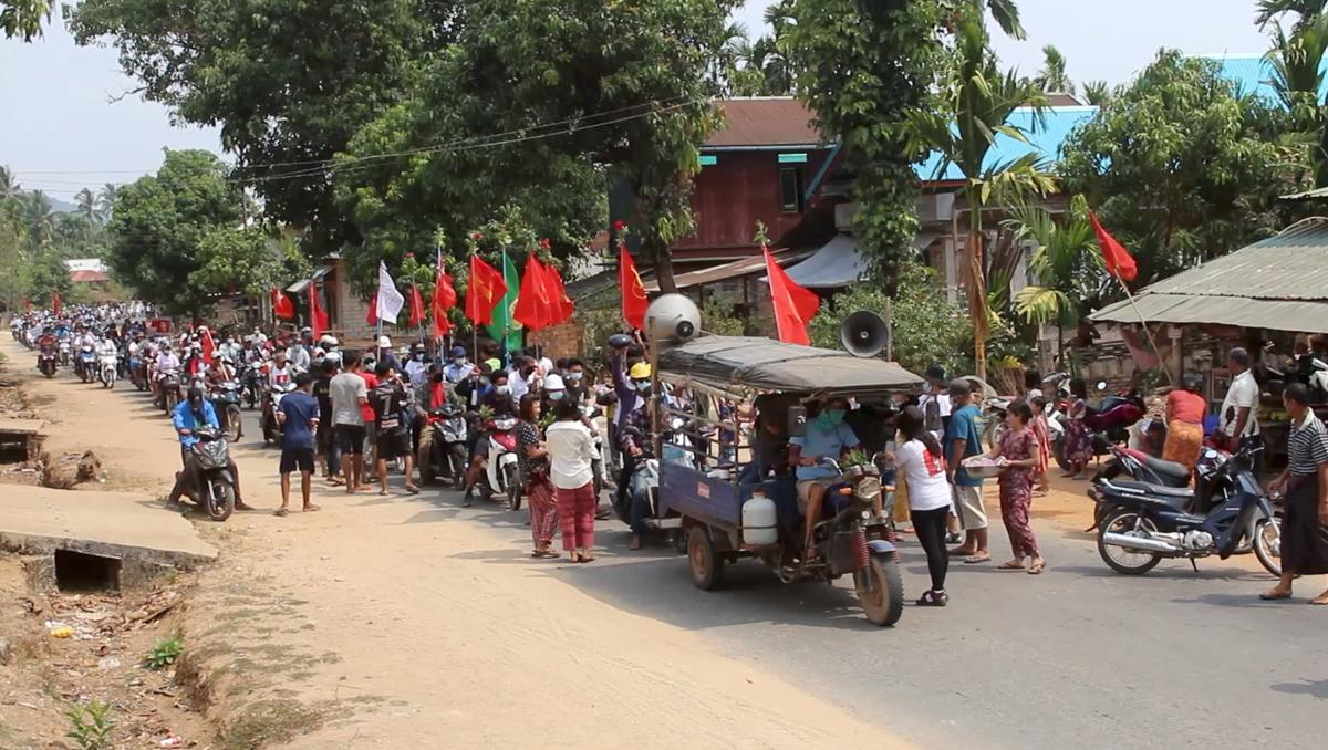 Demonstrators hold flags as they sit on motorcycles during a protest in Launglone, Dawei district