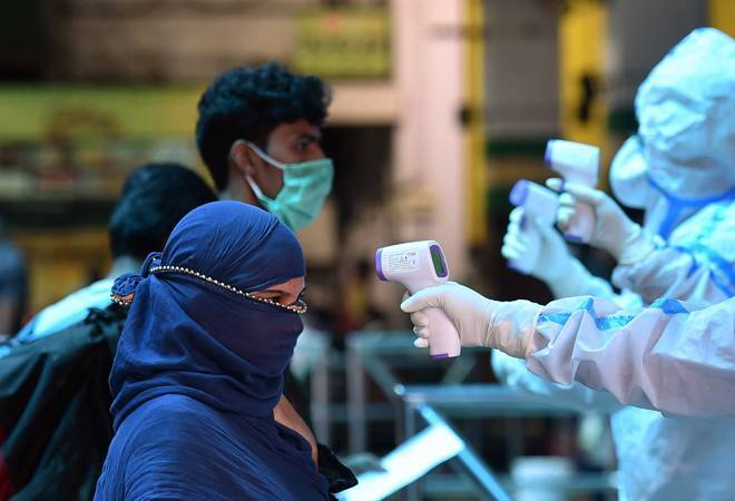 People getting temperature check before entering railway station